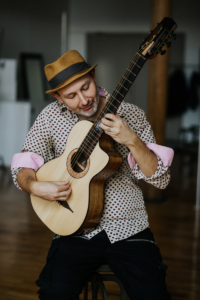 men with hat playing Gypsy Parlor Guitar   Kazourian Luthier